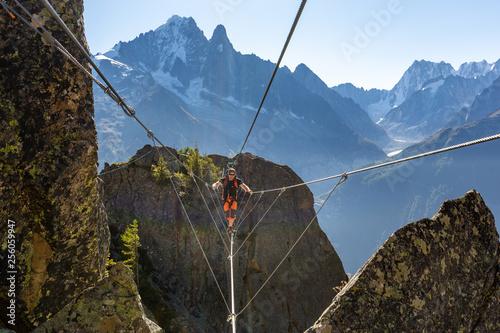Mountaineer crossing cable bridge via ferrata, Chamonix France. Canvas Print