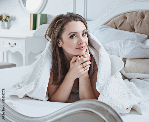 Fotobehang Artist KB Portrait of a smiling woman relaxing on a luxurious bed
