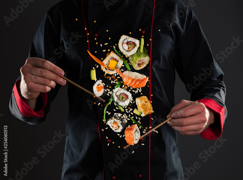 Poster Sushi bar Master chef holding chopsticks with flying sushi