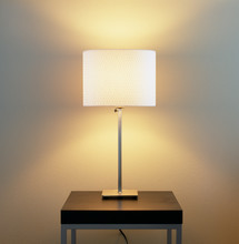 Lamp On Table With Painted Wall Background. Home Energy Use, Electric Lighting Fixtures And Contemporary, Modern Interior Decor Elements.