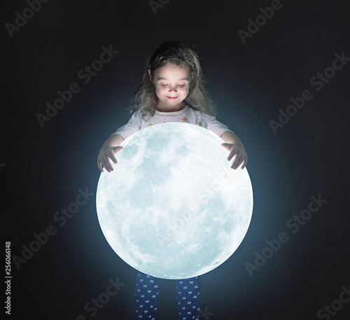 Art portrait of a cute little girl holding a moon