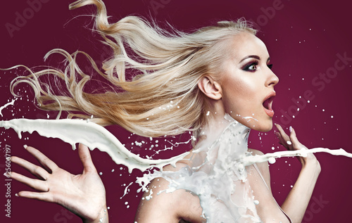Amazed blond lady being poured with white paint