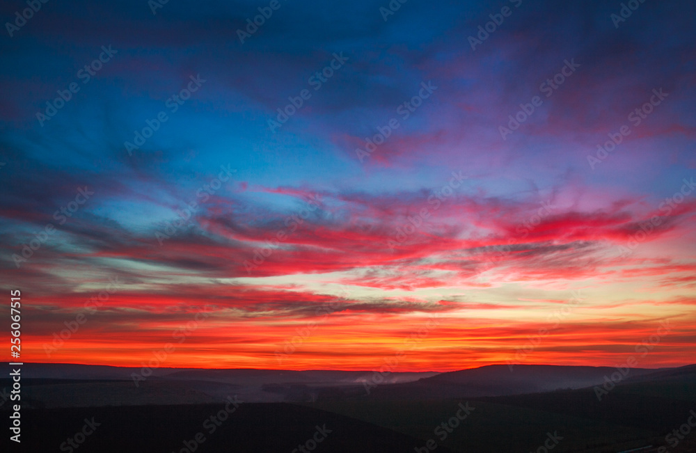 Fototapeta Colorful magnificent sunset in countryside above hills and fields, beauty nature background