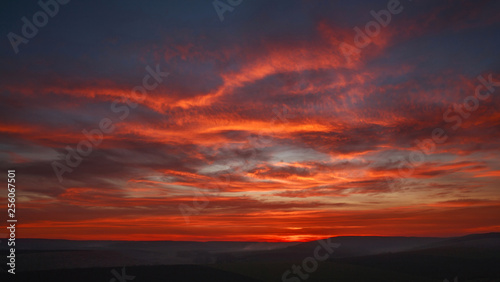 Colorful magnificent sunset in countryside above hills and fields, beauty nature background
