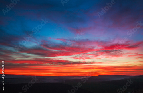 Foto auf Leinwand Blaue Nacht Colorful magnificent sunset in countryside above hills and fields, beauty nature background