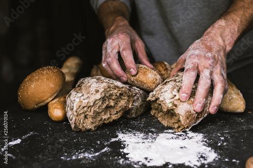 Deurstickers Bakkerij Baker man holding a rustic organic loaf of bread in his hands