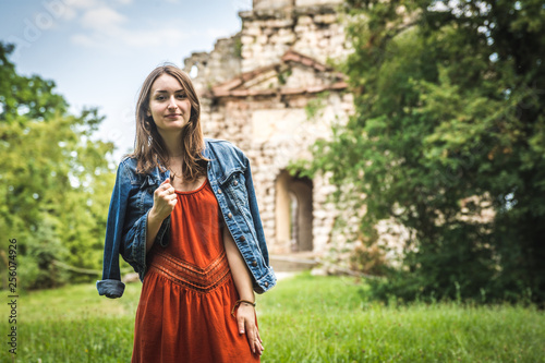 Photo junge Frau vor Ruine / Burg mit kraftvoller Pose