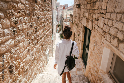 Young girl walking through ancient narrow streets on a beautiful summer day