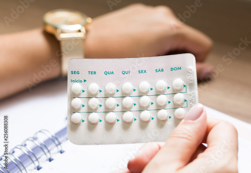 Foto  Woman looking at watch and oral contraceptive pill