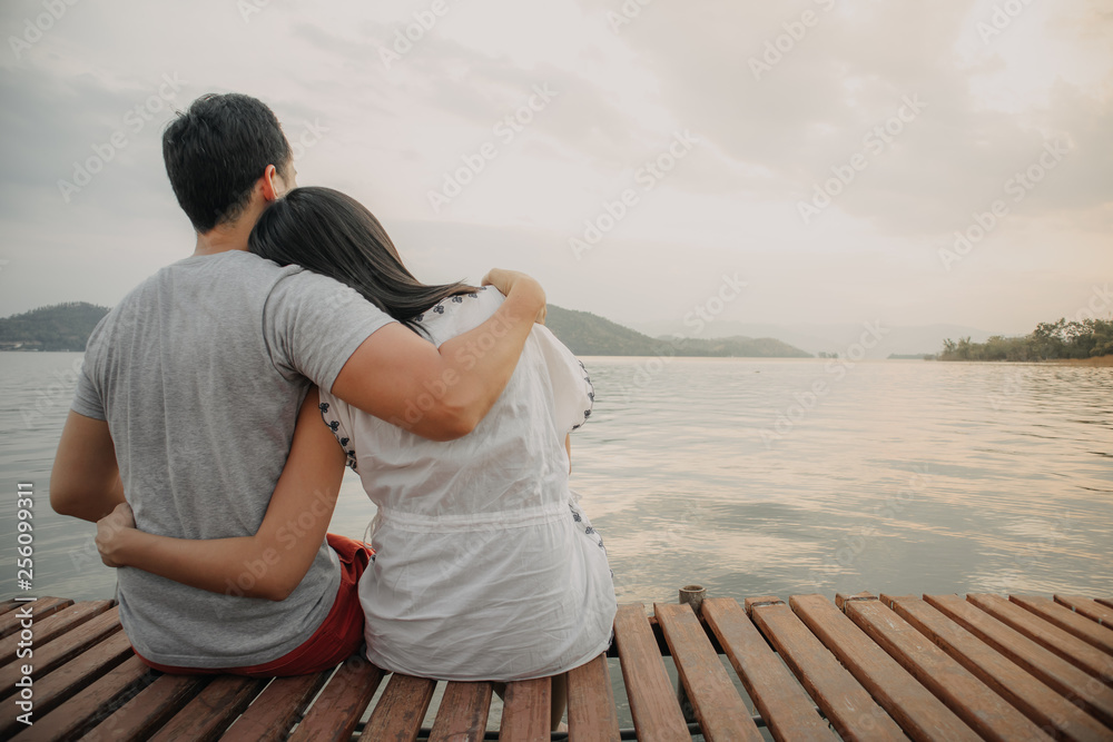 Fototapeta Lover couple hold together and admire the romantic beautiful lake landscape.