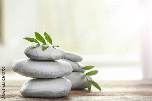 Poster Spa Spa stones and bamboo leaves on table against blurred background. Space for text