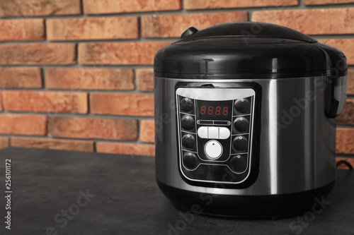 Modern electric multi cooker on table near brick wall. Space for text