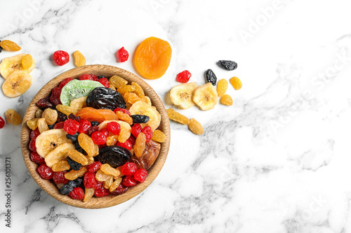Bowl of different dried fruits on marble background, top