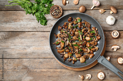 Fototapeta Frying pan of mushrooms on wooden background, flat lay with space for text obraz