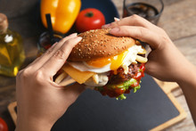 Woman Holding Tasty Burger With Fried Egg Over Table, Closeup