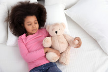 Cute Little African-American Girl With Teddy Bear Sleeping In Bed, Top View