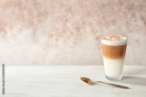 Photographie Glass of caramel macchiato on table against color background