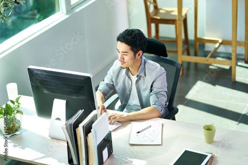 Carta da parati  young asian businessman working in office