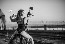 Red-haired Woman In Sexy Lingerie In High Heels Sits On A Motorcycle. Attractive Red-haired Girl Sits On A Motorcycle At Sunset On The Background Of The Industrial Landscape