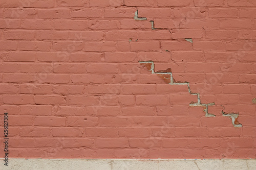 Grungy old red painted brick wall background showing deterioration and chipped paint
