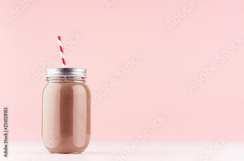 Sweet chocolate milkshake in old fashioned jars with straw, silver cap on light pastel pink background.