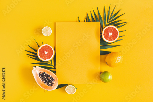 Summer composition. Tropical palm leaves, fruits, yellow paper blank on yellow background. Summer concept. Flat lay, top view, copy space - 256143373