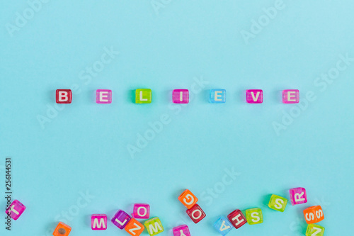 Photo  believe inscription made of colorful cube beads with letters