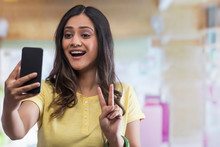 Portrait Of Young Girl Taking Selfie Using Mobile Phone And Showing Victory Sign