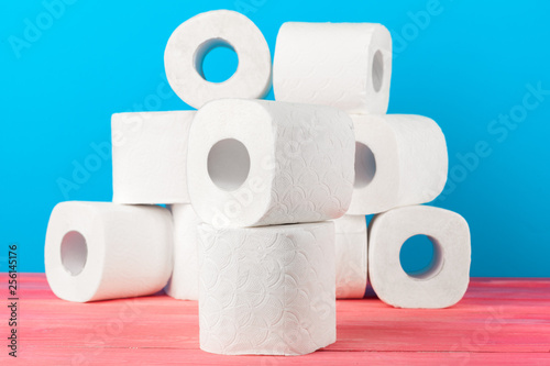 Fotografie, Obraz  Toilet paper rolls stacked against blue background