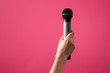 canvas print picture - Female hand with microphone on color background