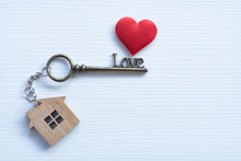 House Key In Heart Shape With Home Keyring On White Wood Background Decorated With Mini Heart
