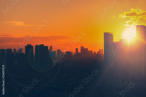 Sunset view of city skyline with bright emotional and powerful energy from light.  First sunlight at dusk.
