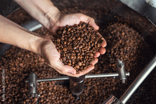 Photo sur Aluminium Café en grains Grains of fresh coffee roasting in hands on the background of the roaster