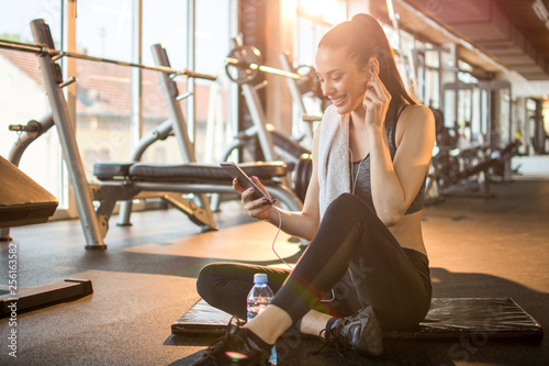 Poster Fitness Beautiful young sportswoman with earphones listening to music on smart phone after sports training in gym