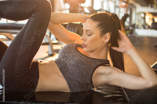 Photo sur Toile Fitness Beautiful young sporty girl doing sit ups on exercise mat in gym