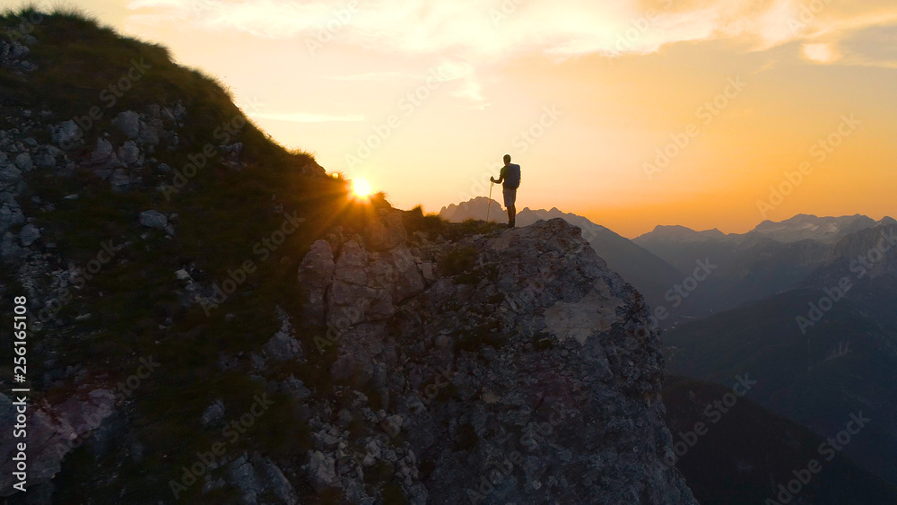 Fototapety, obrazy: LENS FLARE: Stunning sunset illuminates the Alps and hiker standing on a cliff.