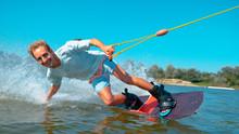 CLOSEUP Smiling Young Caucasian Surfer Wakeboarding, Splashing Water At Camera