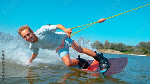 CLOSEUP Smiling young Caucasian surfer wakeboarding, splashing water at camera Tapéta, Fotótapéta