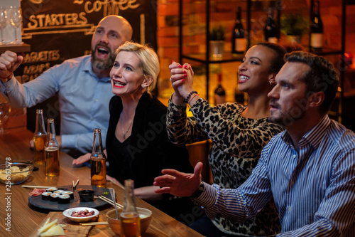 Fototapeta Group of friends watching tv in a cafe behind bar counter obraz na płótnie