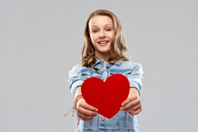 Valentine's Day, Love And People Concept - Smiling Pretty Teenage Girl In Denim Jacket Holding Red Heart Over Grey Background