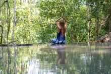 Beautiful Woman Practicing Yoga Near Turquoise Water Of Cascade Waterfall At Deep Tropical Rain Forest, Island Koh Phangan, Thailand