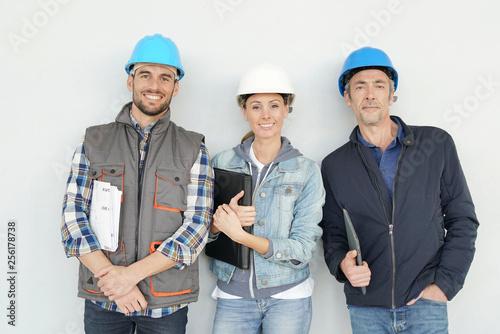 Fotografia  Mixed construction team smiling at camera on grey background