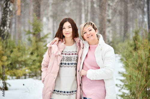 Foto Mother and adult daughter walking in winter forest snowfall
