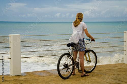 Fototapeta girl on a bike on the pier. obraz na płótnie