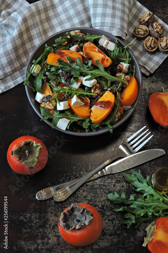 Recess Fitting Appetizer Salad with persimmon, arugula, white cheese and nuts. Keto diet. Keto lunch idea. Pegan diet.