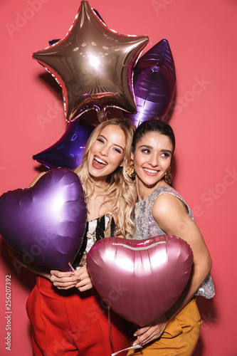 Image of two gorgeous girls 20s in stylish outfit laughing and holding festive b Canvas Print