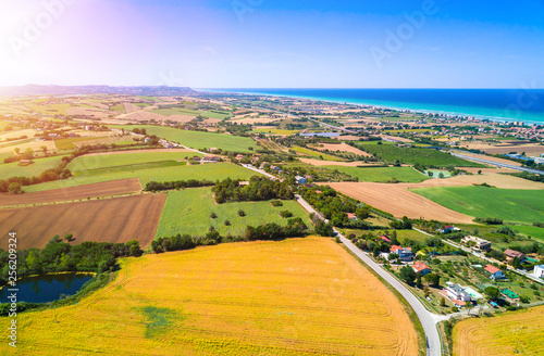 Foto auf AluDibond Orange aerial italian countryside agricultural landscape with sea in the distance on a sunny day during summer
