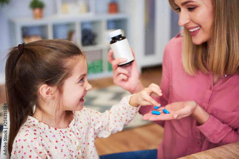 Fototapeta Young mum giving her little daughter the medicine