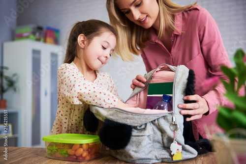 Obraz Young mum and daughter packing backpack for the school - fototapety do salonu