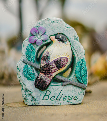 Photo A aged finch white, green alabaster grave statue, that has the words believe on it